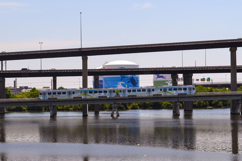 A low-emission commuter train traveling over a bridge on the bay.